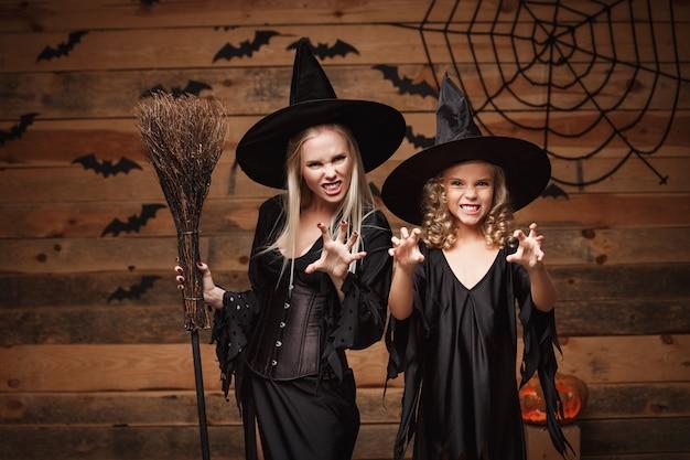 Halloween-konzept - fröhliche mutter und ihre tochter in hexenkostümen, die halloween feiern, das mit gebogenen kürbissen über fledermäusen und spinnennetz auf holzwand aufwirft.