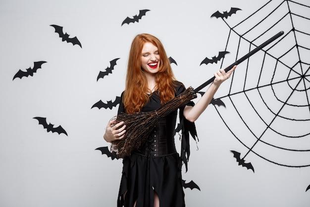 Halloween-konzept glückliche elegante hexe genießt das spielen mit besenstiel-halloween-party