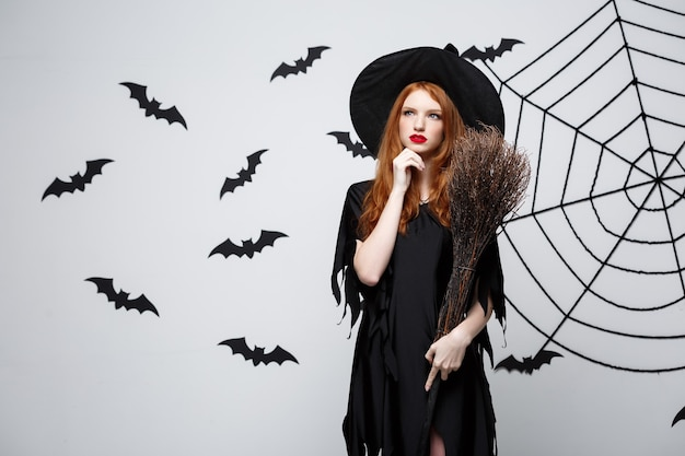 Halloween-konzept glückliche elegante hexe mit besenstiel halloween, die an etwas denkt