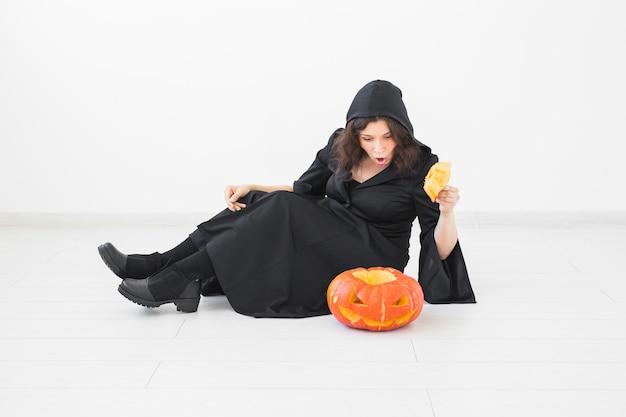 Halloween-konzept - glückliche hexe mit kürbis jack-o'-laterne auf hellem hintergrund.