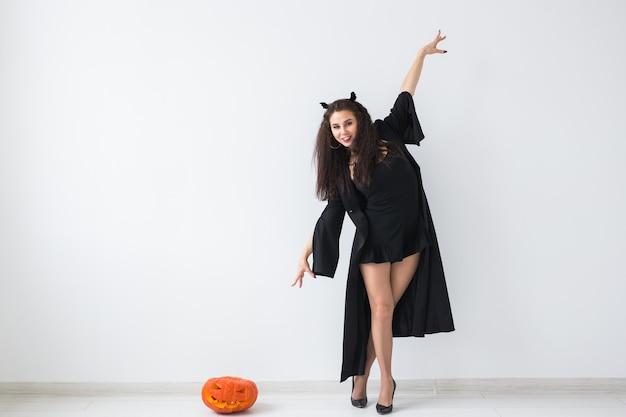 Halloween-konzept - glückliche hexe mit kürbis-kürbislaterne auf heller wand mit kopienraum.
