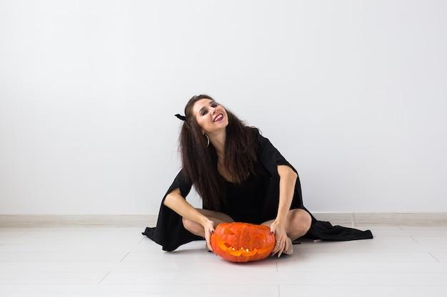Halloween-konzept - glückliche hexe mit kürbis-kürbislaterne.