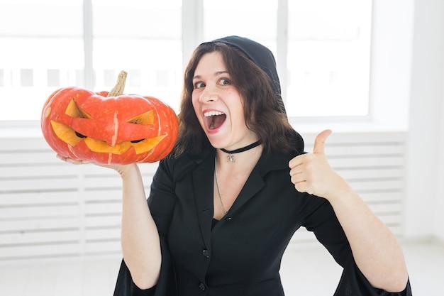 Halloween-konzept - glückliche hexe zeigt daumen hoch geste mit kürbis jack-o'-laterne auf hellem hintergrund