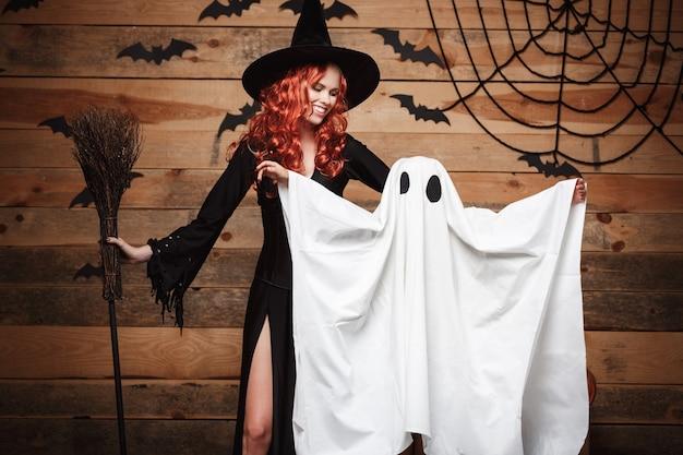 Halloween-konzept - hexenmutter und kleiner weißer geist, die süßes oder saures tun, um halloween zu feiern, das mit gebogenen kürbissen über fledermäusen und spinnennetz auf hölzernem studiohintergrund posiert.
