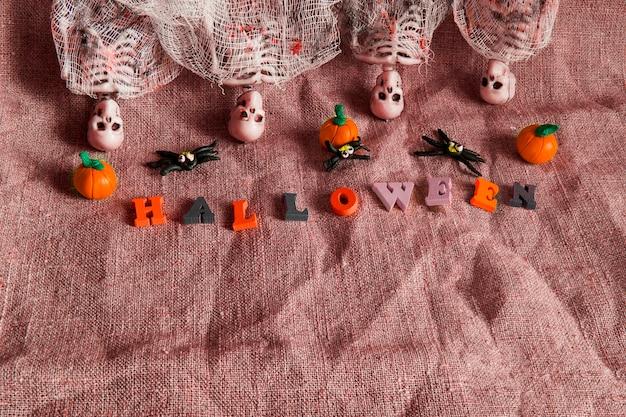 Halloween-konzept mit kürbis, skelett und spielzeugspinnen auf zerknittertem grauem hintergrund