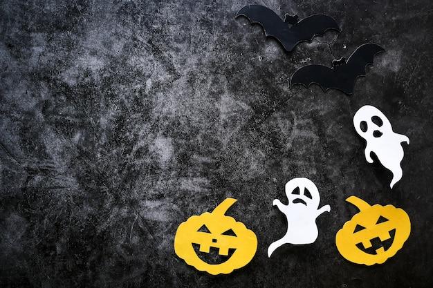 Halloween-konzept mit kürbisen, geistern und schlägern schnitt papier auf schwarzem konkretem hintergrund.