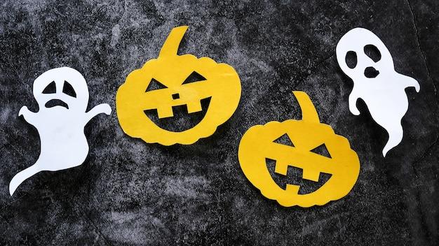 Halloween-konzept mit kürbisen und geistern schnitt papier auf schwarzem konkretem hintergrund.