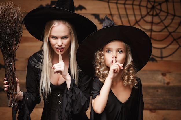 Halloween-konzept - nahaufnahme kaukasische mutter und ihre tochter in hexenkostümen, die halloween feiern, das mit gebogenen kürbissen über fledermäusen und spinnennetz auf holzwand aufwirft.