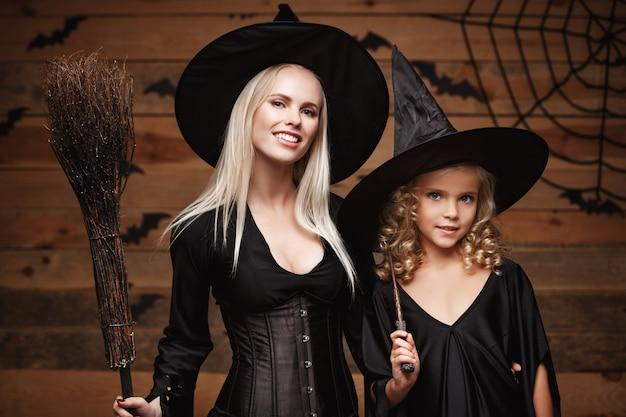 Halloween-konzept - nahaufnahme kaukasische mutter und ihre tochter in hexenkostümen feiern halloween, das auf hölzerner wand aufwirft.