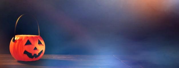 Halloween-konzept - orangefarbene kürbislaterne aus kunststoff auf einem dunklen holztisch mit verschwommenem funkeln im hintergrund, süßes oder saures, nahaufnahme