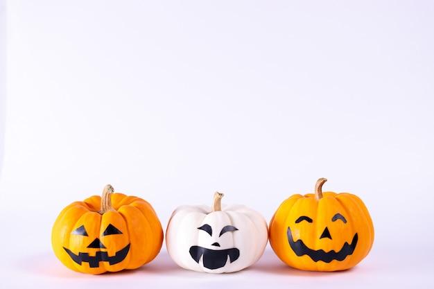 Halloween-konzept. orangefarbene und weiße kürbisse auf weißem hintergrund.