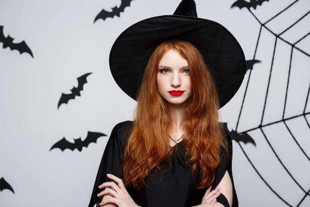 Halloween-konzept - schöne hexe, die hand hält und über grauer wand lächelt.