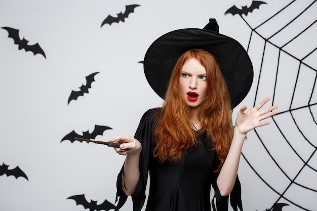 Halloween-konzept - schöne hexe, die mit zauberstab auf grauer wand spielt.