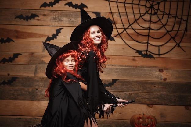 Halloween-konzept - schöne kaukasisch mutter und ihre tochter mit langen roten haaren in hexenkostüme feiern halloween posiert