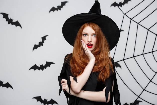 Halloween-konzept - schöne kaukasische hexe, die mit etwas über grauer wand schockiert.