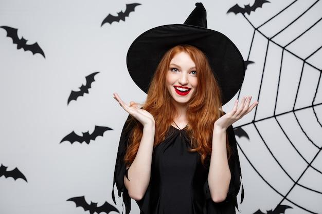 Halloween-konzept - schöne kaukasische hexe, die mit etwas über grauer wand überrascht.