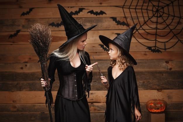 Halloween-konzept - stressige hexenmutter, die ihre tochter in hexenkostümen unterrichtet, die halloween mit gebogenen kürbissen über fledermäusen und spinnennetz auf holzwand feiern.
