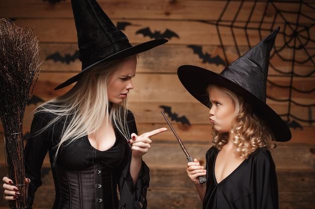 Halloween-konzept - stressige hexenmutter, die ihre tochter in hexenkostümen unterrichtet, die halloween über fledermäusen und spinnennetz auf holzwand feiern.