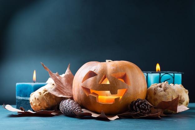 Halloween-kürbis auf blau mit kerzen und herbstlaub und kiefernkegeln.