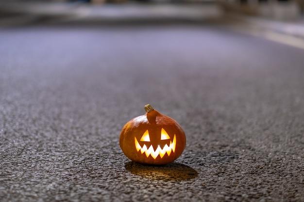 Halloween-kürbis auf dem asphalt auf einer verlassenen stadtstraße in der nacht