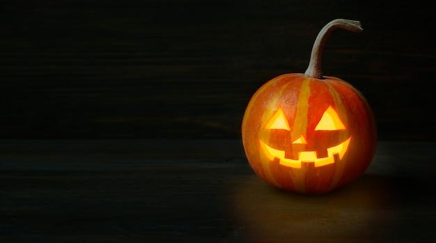 Halloween-kürbis auf einem dunklen holztisch. halloween-hintergrund. banner. platz kopieren.