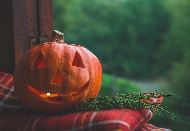 Halloween-kürbis auf einem gemütlichen fensterbrett mit einem roten plaid. ganzer kürbis und wunderkerze im freien. fröhliches halloween! der herbst ist gemütlich.