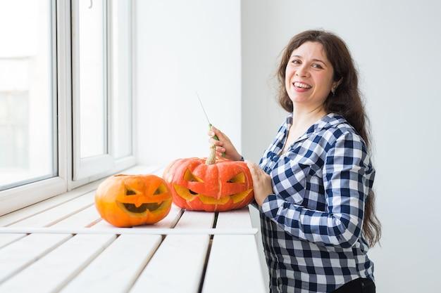 Halloween-kürbis-ausschnittprozess. junge frau, die jack-o-laterne macht.
