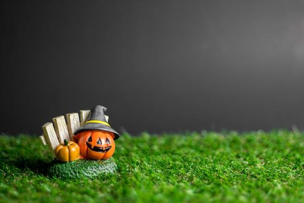 Halloween-kürbis, der einen hut auf dem gras trägt.