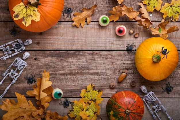 Halloween-kürbis. festliches herbstdekor aus kürbissen, blättern, spinnen, skeletten und lustigen augen auf altem holzhintergrund. flache herbstkomposition mit kopienraum.