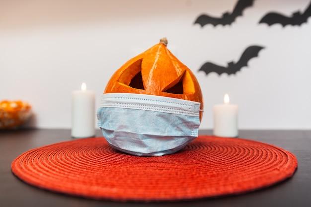 Halloween kürbis in medizinischer maske steht auf dem tisch