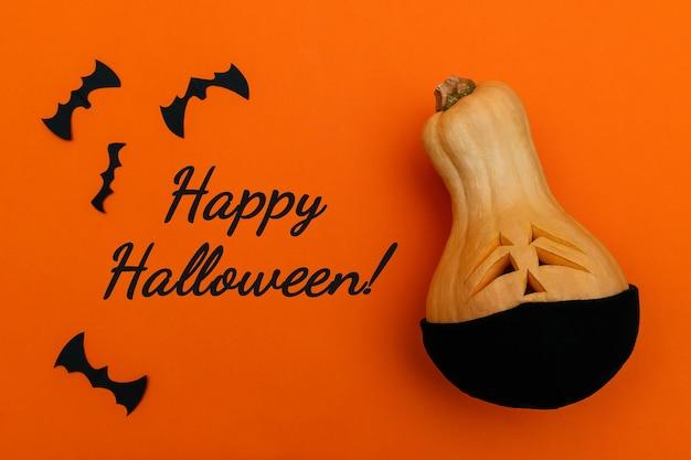 Halloween-kürbis in medizinischer schutzmaske und bathalloween- und covid19-konzept
