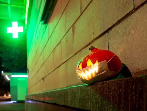 Halloween-kürbis mit einer schutzmaske im gesicht vor dem hintergrund eines apothekenkreuzes