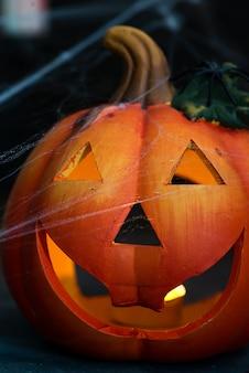 Halloween-kürbis mit furchtsamem auf dem fenster nachts