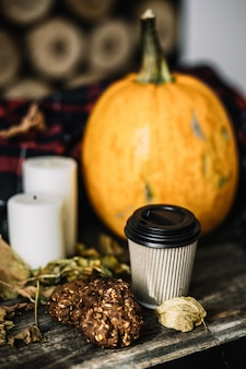 Halloween-kürbis mit kaffeetasse auf holz.