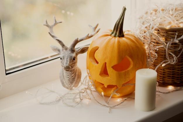 Halloween-kürbis mit kerze am fenster.