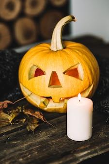 Halloween kürbis mit kerze auf holz.