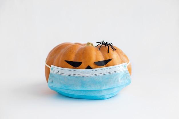 Halloween-kürbis mit medizinischer maske und spinne auf weißem hintergrund kürbis-jack mit gesichtsmaske