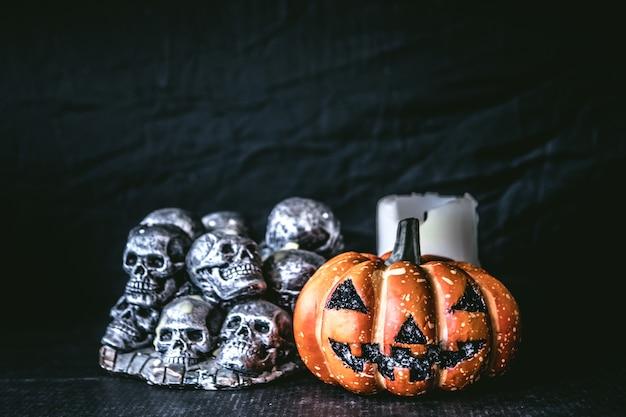 Halloween-kürbis mit schädeln und kerze auf einem schwarzen hintergrund.