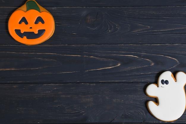 Halloween-kürbis- und -geistplätzchen auf hölzernem schreibtisch