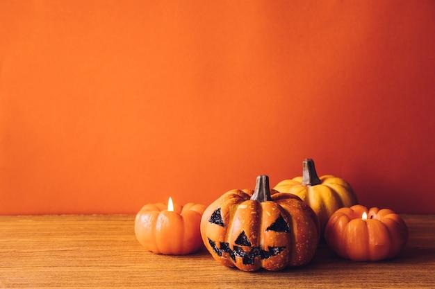 Halloween-kürbise mit kerzenlicht auf einem orange farbhintergrund. freier platz für text