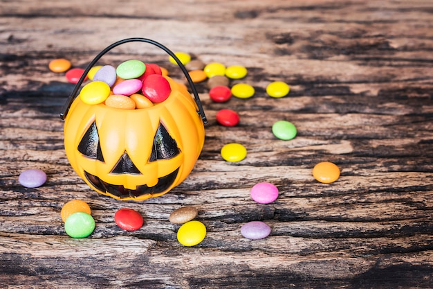 Halloween-kürbisgesichtseimer mit bunter süßigkeit nach innen auf alter hölzerner beschaffenheit