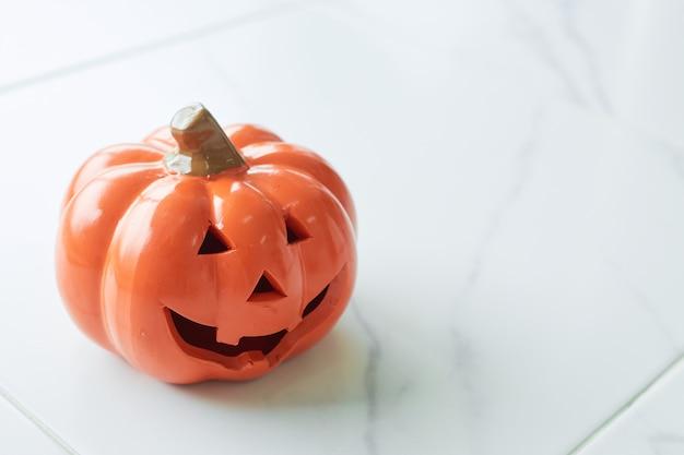 Halloween-kürbishauptsteckfassungslaterne auf weißem marmorboden