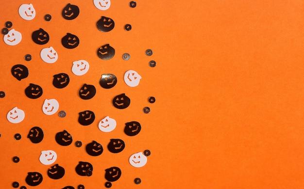 Halloween-kürbiskonfettidekorationen auf orange hintergrund.