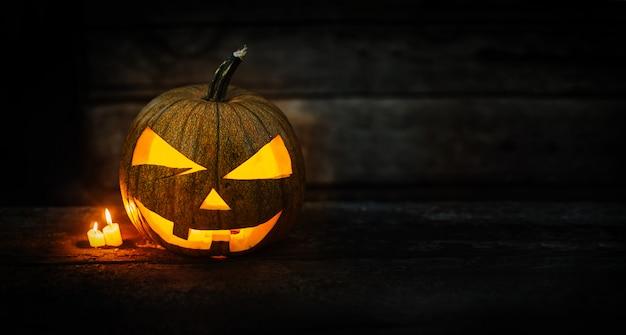 Halloween-kürbiskopf mit brennenden kerzen