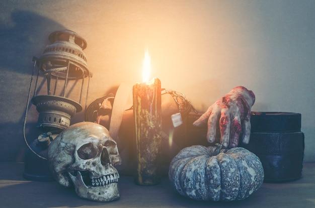 Halloween-kürbiskopfsteckfassungslaterne und menschlicher schädel auf hölzernem hintergrund