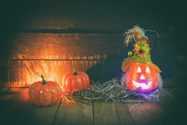 Halloween-kürbislaterne mit trockenem stroh auf hölzernem
