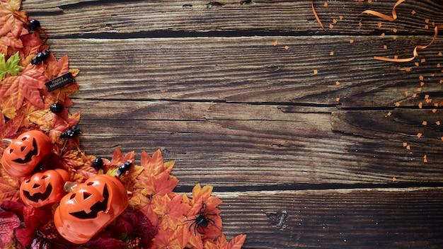 Halloween-kürbisse mit herbstherbstblättern über holz