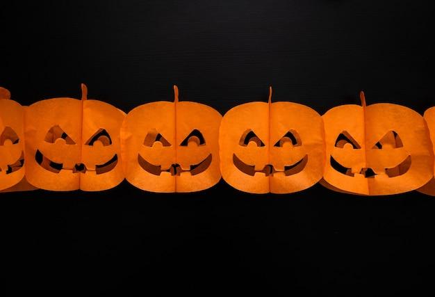 Halloween kürbisse papiergirlande mit glücklichem gesicht auf dunklem hintergrund