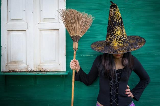 Halloween-kunstdesign, schöne junge frau in hexenhut und -besen in ihrer hand