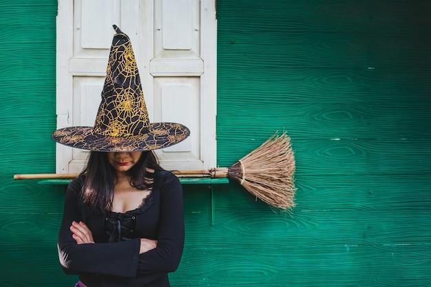 Halloween-kunstdesign, schöne junge frau in hexenhut und -besen